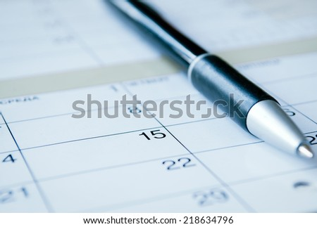 Ballpoint pen lying on a calendar with selective focus to the date of the 15th, calendar at an oblique angle - stock photo