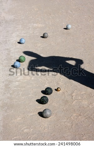 Balls and man shadow on the ground of bocce ball court - stock photo