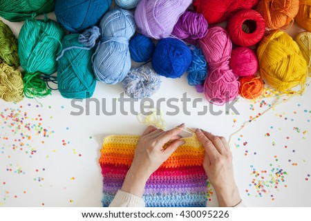 Balls of colored yarn. View from above. All the colors of the rainbow. Sample knit. Women's hands are knitted. Crochet. - stock photo