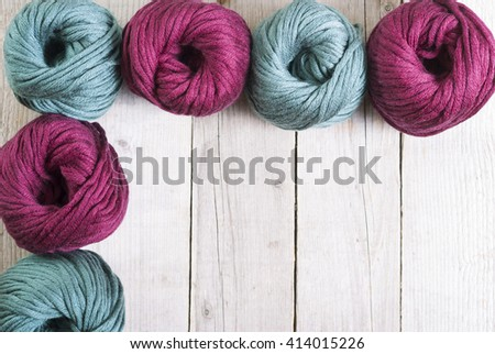 balls of wool in a row on rusty wooden - stock photo