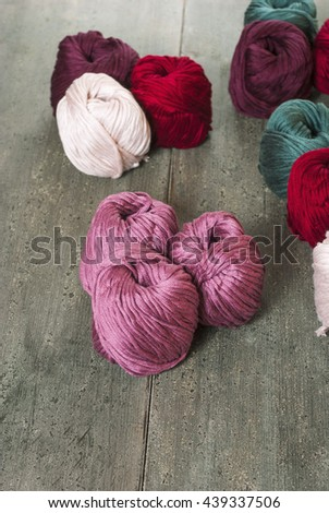 balls of wool on old wood table  - stock photo