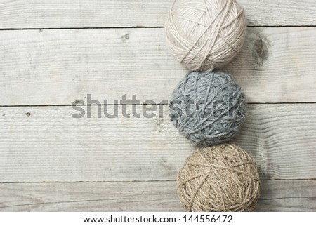 balls of wool on wooden background - stock photo
