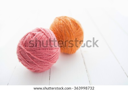 Balls of yarn for knitting on wooden table boards - stock photo