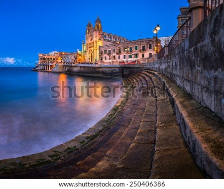 Balluta Bay and Church of Our Lady of Mount Carmel in Saint Julien, Malta - stock photo