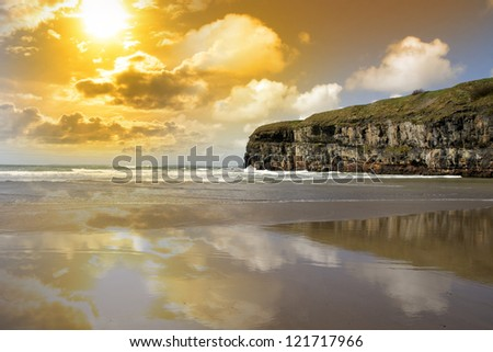 Ballybunion beach and cliffs on the Atlantic coast in Ireland with waves crashing on the cliffs at sunset - stock photo