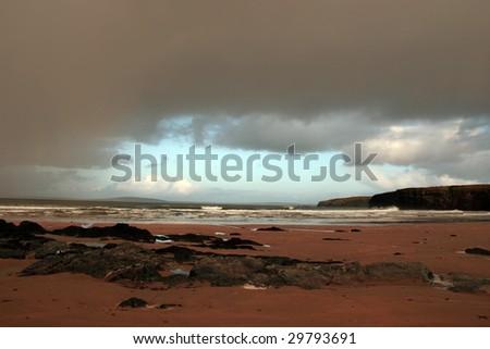 ballybunion beach as a storm gathers power on the horizon - stock photo
