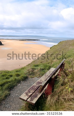 ballybunion bench in winter with view of castle beach and cliffs - stock photo