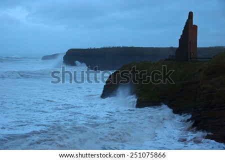Ballybunion castle and cliffs during a very bad storm with crashing waves - stock photo