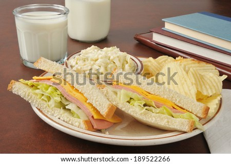 Baloney and cheese sandwich with coleslaw near school books