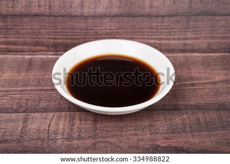 Balsamic vinegar in a white bowl over rustic wooden background - stock photo