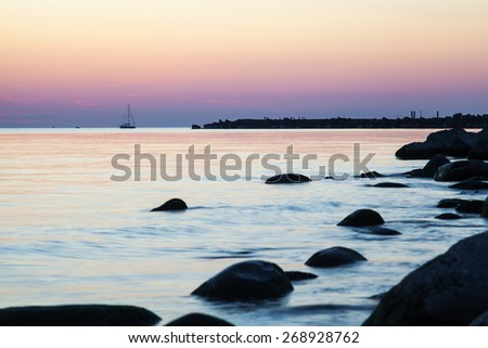Baltic sea at magenta sunset while calm windless weather. There are sailing yacht along breakwater with people walking on it and dark stones in foreground in water. - stock photo