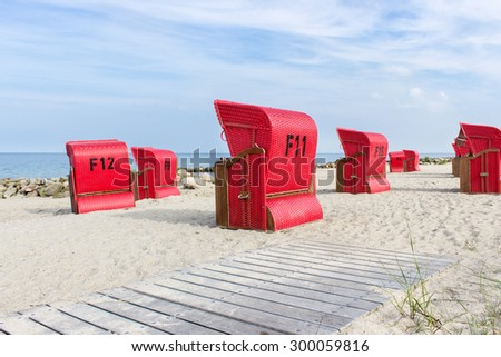 Baltic Sea beach with red beach chairs and blue sky / beach chairs by the sea / Baltic Sea