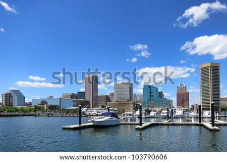 Baltimore Maryland downtown business district skyline scenic cityscape panoramic with pleasure boats in port marina at Inner Harbor over blue sky - stock photo
