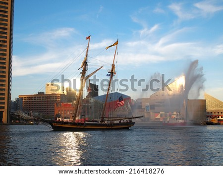 BALTIMORE, MD -  SEPTEMBER 10, 2014: Tall ship Pride of Baltimore and a Baltimore City fire boat celebrate the 200th anniversary of America's national anthem in the Inner Harbor in Baltimore, MD. - stock photo
