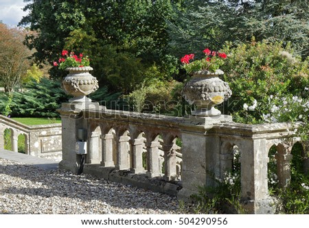 Balustrade in an English Formal Landscape garden with ornamental stone planters filled with geraniums