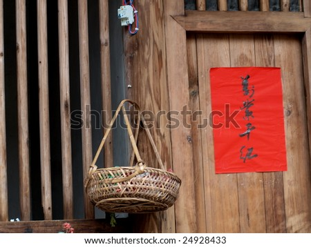 """Bamboo basket  by wooden door. On the door there was a spring festival scroll , the word on it means """"a blaze of color"""" for celebrating the Chinese spring festival . - stock photo"""