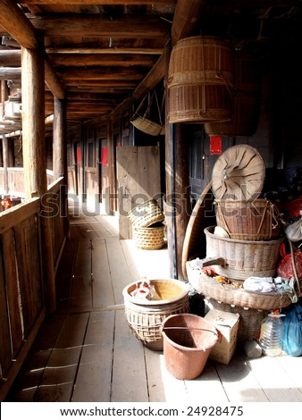 Bamboo baskets and other cultivate utensil in wooden aisle of an  house in the village of China. - stock photo