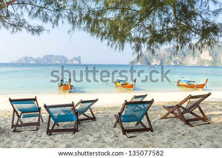 Bamboo beach chairs and traditional long-tail boats on beautiful bay of Koh Phi Phi Island Thailand - stock photo
