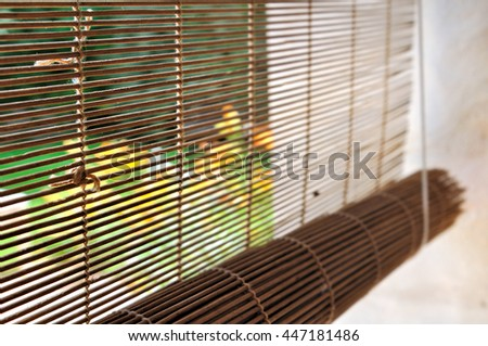 bamboo blind at a window overlooking garden  - stock photo