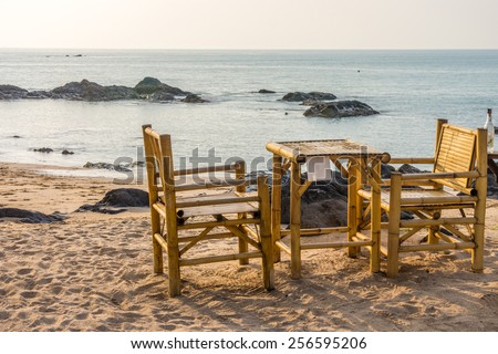 Bamboo chairs and table with clear sky on Pak Weep beach in Southern Thailand in the evening