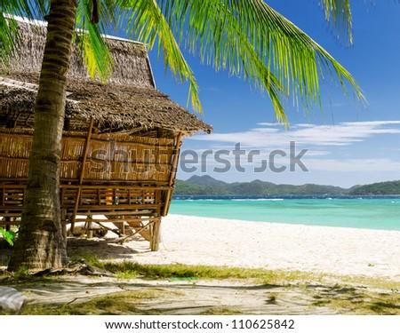 Bamboo hut on a tropical beach. - stock photo