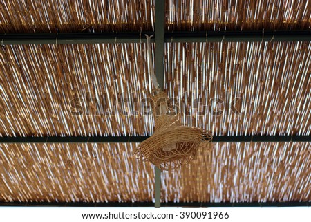 Bamboo lamp hanging and swinging in the wind - stock photo