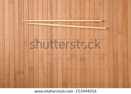 Bamboo mat and chopsticks food background  - stock photo