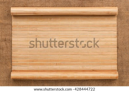 Bamboo mat in the form of a manuscript on sackcloth, top view - stock photo