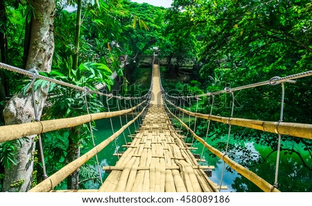 Bamboo pedestrian hanging bridge over river in tropical forest, Bohol, Philippines, Southeast Asia - stock photo