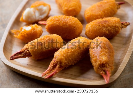 Bamboo tray with breaded crab claws, close-up, studio shot - stock photo