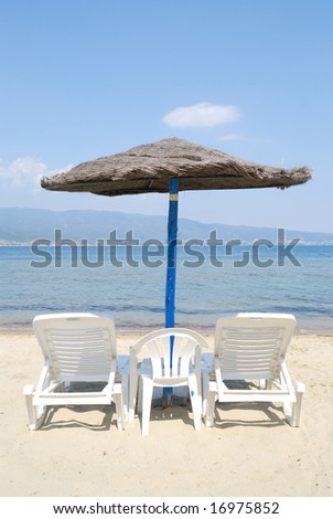 Bamboo umbrella with chairs on beautiful beach