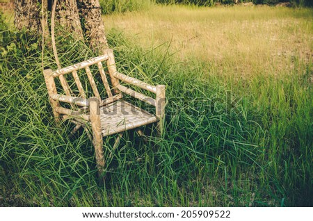 Bamboo wooden chairs on grass field in countryside Thailand vintage - stock photo