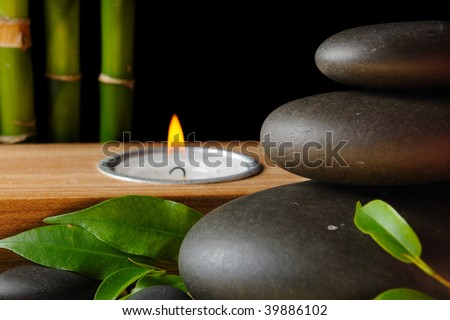 Bamboo,zen stones and candlestick on the black background