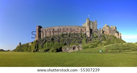 bamburgh castle in northumberland on the north east coast of england, sitting high on a rocky plateau it is one of the larget inhabited castles in the uk - stock photo