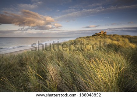 Bamburgh Castle on the Northumberland coast. The Farne Islands are visible on the horizon.  - stock photo