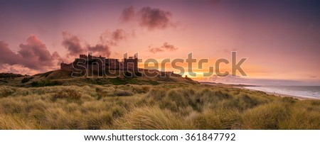 Bamburgh Castle Panorama / The Iconic Bamburgh Castle on the Northumberland Coastline in panorama at sunset - stock photo