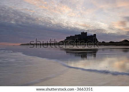 Bamburgh Castle, waves and beach at sunrise
