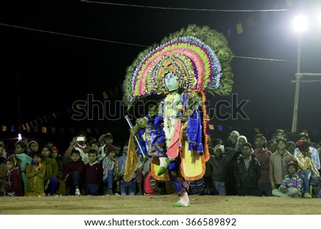 BAMNIA, PURULIA, WEST BENGAL , INDIA - DECEMBER 23RD 2015 : Dancer dressed as Lord Kirishna posing at Chhau Dance. It is very popular Indian tribal martial dance performed at night amongst spectators. - stock photo