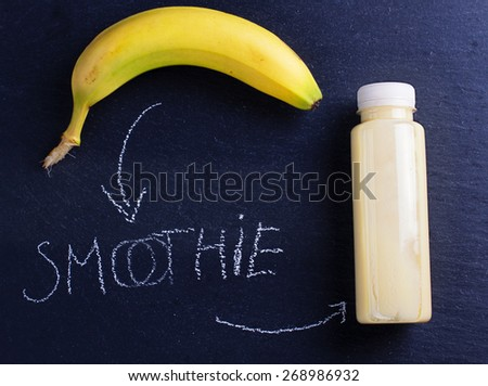 Banana and bottle of smoothies on a table, smoothie preparation - stock photo