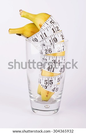 Banana and measurement tape in a clear glass on white background - stock photo