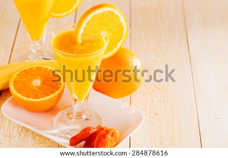 Banana and orange smoothie with  dried apricots on a light wooden background.