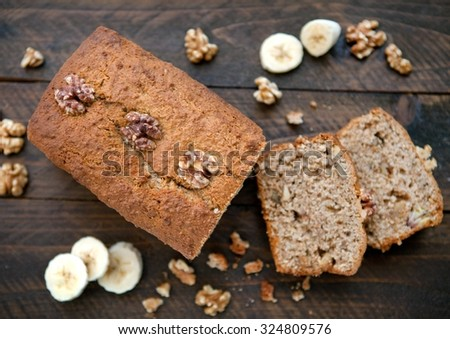 Banana and Walnut loaf cake cut open on wooden board - stock photo