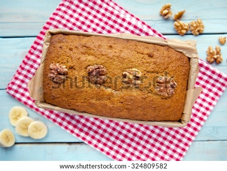 Banana and Walnut loaf cake on red and white gingham cloth - stock photo