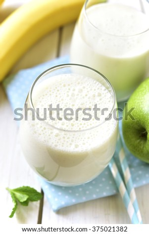 Banana apple smoothie for a healthy breakfast on a white wooden table.