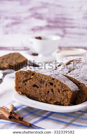 Banana bread with powdered sugar, cream cheese, cinnamon and dates on white wooden background.