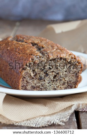 Banana bread with walnuts in the baking paper on the wooden table - stock photo