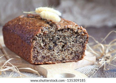 Banana bread with walnuts on the kitchen board in rustic style