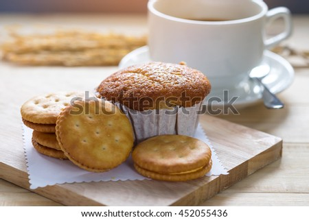 Banana cake  and  biscuit  with coffee cup on wooden table.