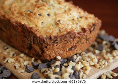 Banana cake on cutting board with chocolate chip it and nuts - stock photo
