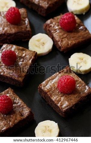 Banana chocolate brownies - Healthy Brownies using mashed bananas on dark black background, selective focus - stock photo